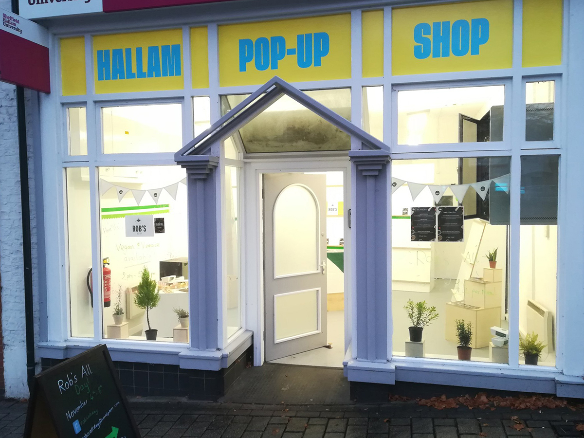 The Hallam Pop-Up Shop lit at night